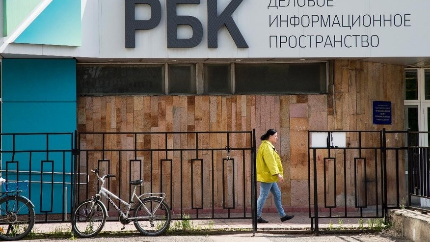 In this photo taken on Thursday, May  12, 2016, a woman walks past the RBC, Media Group Russian Business Consulting holding firm headquarters which includes the first Russian business television company building in Moscow, Russia. Three key editors at top Russian media holding firm RBC said Friday they have resigned amid a flurry of probes and police raids around the company. (AP Photo/Alexander Zemlianichenko)
