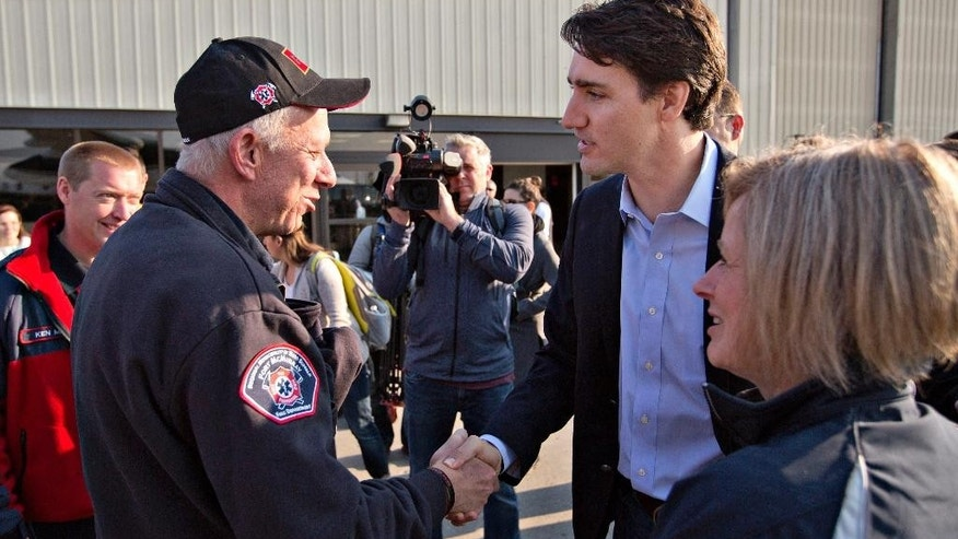 Prime Minister Justin Trudeau shakes hands with Fort McMurray fire chief Darby Allen as Alberta Premier Rachel Notley, right, looks on in Edmonton, Friday, May 13, 2016, before a flight to Fort McMurray. Trudeau is making the visit to see first-hand the devastation caused by the wildfire that forced the evacuation of the city.  (Jason Franson/The Canadian Press via AP) MANDATORY CREDIT