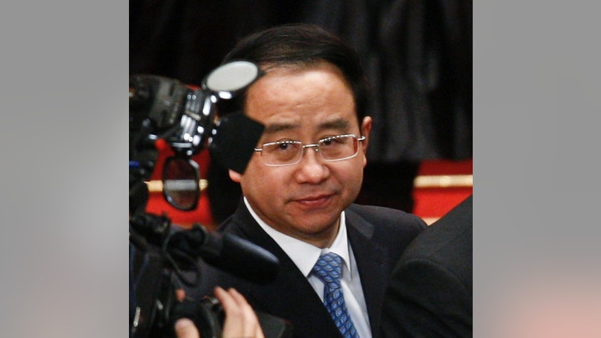 FILE - In this March 14, 2012, file photo, Ling Jihua, a loyal aide and confidante to President Hu Jintao, is seen as Chinese President Hu Jintao signs a document after attending the closing ceremony of the National People's Congress at the Great Hall of the People in Beijing. Chinese prosecutors have indicted the former top aide to ex-President Hu Jintao on charges of taking bribes, illegally obtaining state secrets and abuse of power, state media reported Friday, May 13, 2016 in the latest high-profile blow in President Xi Jinping's sweeping crackdown on corruption. (AP Photo/Andy Wong, File)