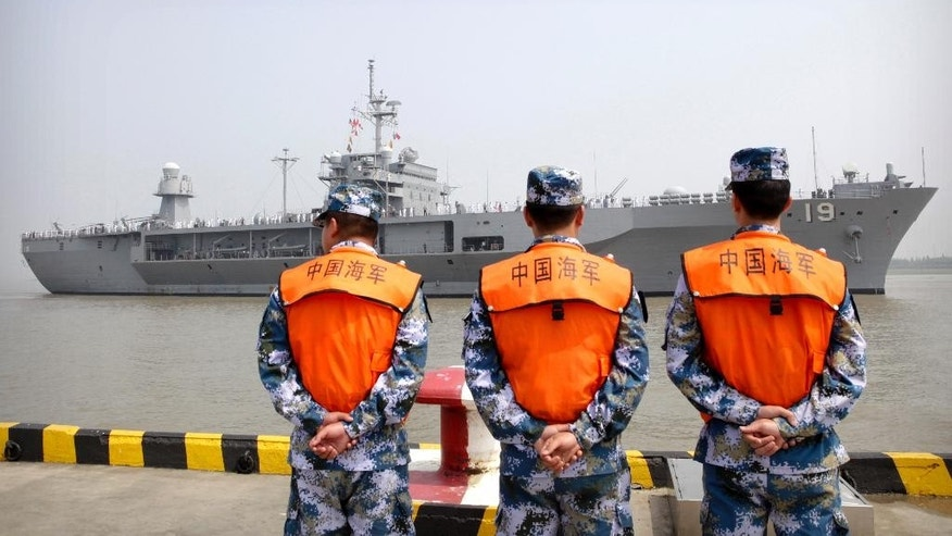 FILE - In this May 6, 2016, file photo, soldiers from the Chinese People's Liberation Army (PLA) Navy watch as the USS Blue Ridge arrives at a port in Shanghai. Seeking to calm escalating tensions in the South China Sea, top generals from China and the U.S. spoke by phone Thursday, May 12, 2016, and said they were ready to work out an effective mechanism to prevent confrontation and maintain stability in the region. (AP Photo, File)