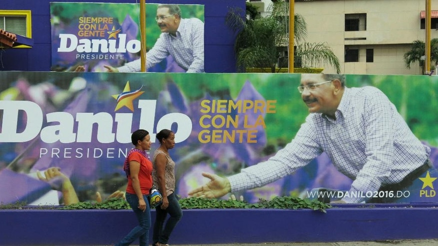 CORRECTS BYLINE - In this April 25, 2016 photo, women walk in front of a campaign billboard for incumbent President Danilo Medina's re-election campaign, in Santo Domingo, Dominican Republic. Dominicans will vote in a general election on May 15. Polls show the president cruising toward re-election, and he may even win more than 50 percent in Sunday's vote and avoid a runoff. (AP Photo/Ezequiel Lopez)