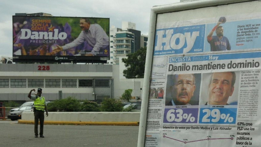 CORRECTS BYLINE - In this April 25, 2016 photo, the front page of Dominican newspaper shows the results of a recent Gallup opinion poll with incumbent, President Danilo Medina ahead in the polls, in Santo Domingo, Dominican Republic. Anger over higher sales taxes and university fees to help close a budget deficit when Medina came into office has largely faded. Many say they are pleased with public spending that has included the construction of about 2,500 new schools, as well as improvements to roads and drainage in the flood-prone nation. The government also draws praise for expanding the school day and providing two free meals per day for students. (AP Photo/Ezequiel Lopez)