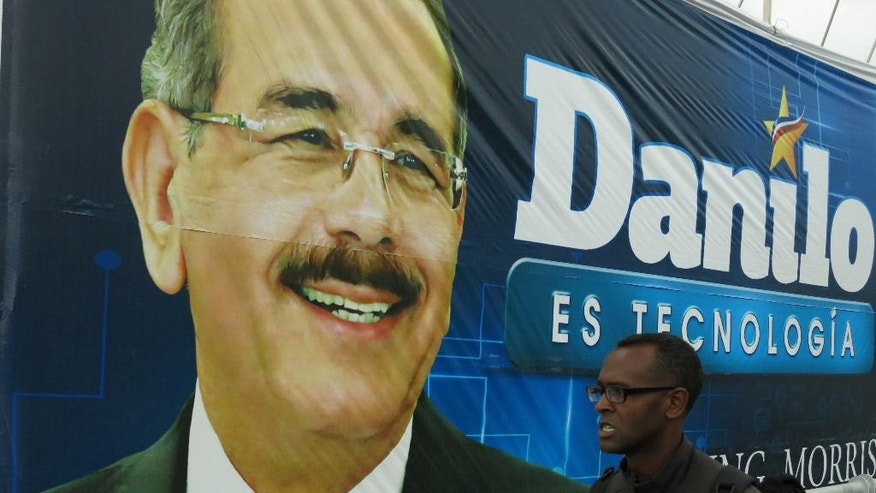 CORRECTS BYLINE - In this April 25, 2016 photo, a man walks on a pedestrian bridge where a Danilo Medina campaign billboard hangs in Santo Domingo, Dominican Republic. Medina, a 64-year-old economist by training and career technocrat, is facing seven opponents in the first electoral round. (AP Photo/Ezequiel Lopez)
