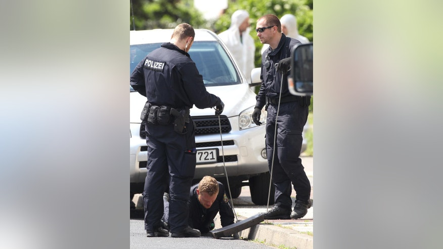 Policemen looking for evidence in Dessau-Rosslau, Germany,  Friday May 13,  2016. German police searching for a missing Chinese student say they have found the body of a woman with several facial and head injuries. The body was discovered Friday in the eastern town of Dessau-Rosslau, where the woman from China had been studying. Friends reported the unnamed 25-year-old missing Thursday, a day after she had last been seen going out for a jog.   (Sebastian Willnow/dpa via AP)