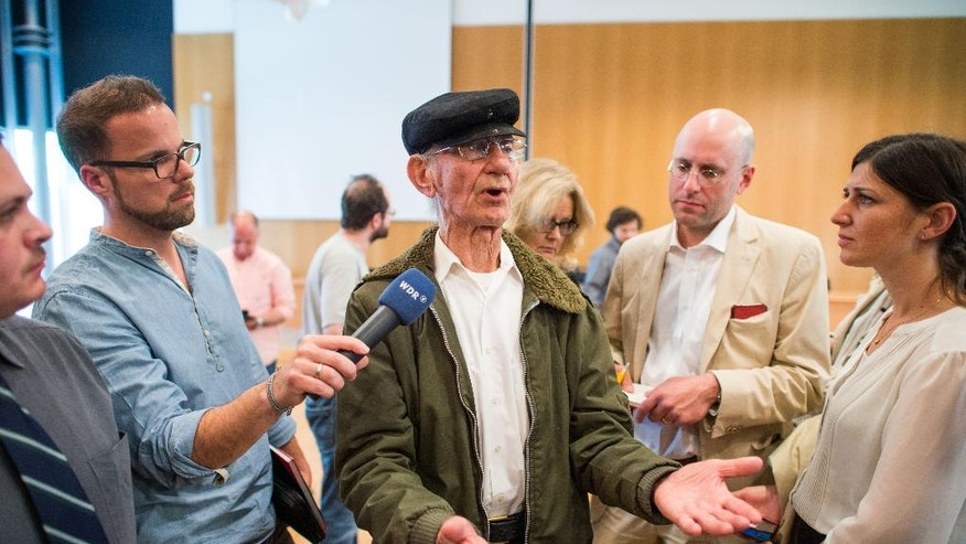 Auschwitz survivor  Joshua Kaufman,   speaks to the media in the courtroom  during the trial against  defendant Reinhold Hanning in Detmold, Germany, Friday May 13, 2016.  The German court trying 94-year-old ex-SS sergeant Hanning,  who served as an Auschwitz death camp guard has declined to hear evidence from the  Auschwitz survivor who traveled from the U.S. The 88-year-old Joshua Kaufman hadn't been invited to testify but some of the Holocaust survivors and relatives who joined the trial as co-plaintiffs hoped he could tell the Detmold state court about how he had to remove corpses from gas chambers.   ( Bernd Thissen/Pool Photo via AP)