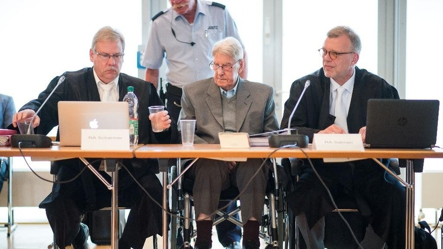 94-year-old former SS guard at the Auschwitz death camp Reinhold Hanning, center, sits between his lawyers Andreas Scharmer, left, and Johannes Salmen, right, during his trial in Detmold, Germany, Friday, May 13, 2016. Hanning faces trial for 170,000 counts of accessory to murder, the first of up to four cases being brought to court this year by German  prosecutors to punish Nazi war crimes. (Bernd Thissen/Pool Photo via AP)