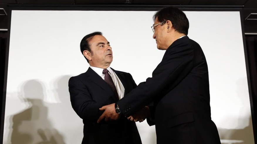 "Nissan Motor Co. President and CEO Carlos Ghosn, left, and Mitsubishi Motors Corp. Chairman and CEO Osamu Masuko shake hands after their joint press conference in Yokohama, near Tokyo, Thursday, May 12, 2016. Nissan is taking a 34 percent stake in scandal-ridden Mitsubishi Motors in what Ghosn said was ""a win-win"" deal. Ghosn said Nissan will invest 237 billion yen ($2.2 billion) to become the top investor in Mitsubishi Motors. (AP Photo/Eugene Hoshiko)"