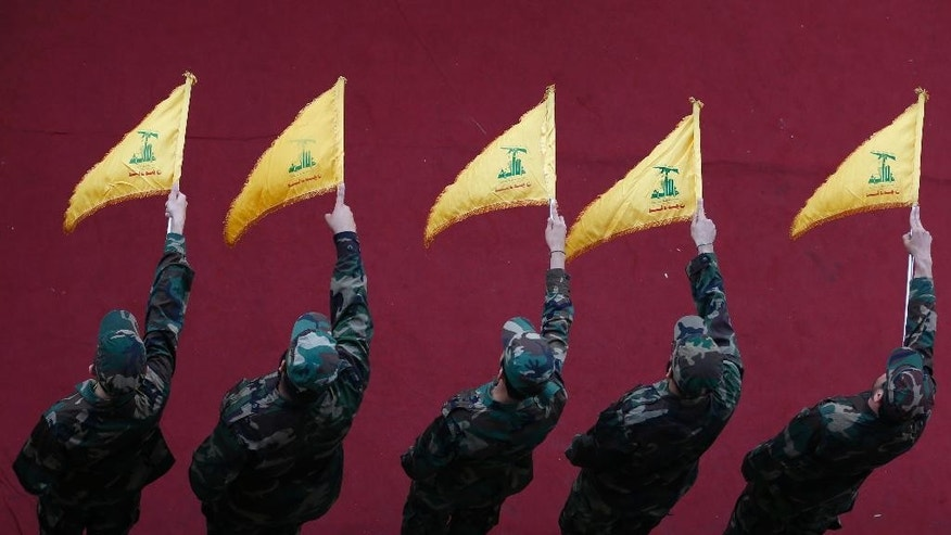 Hezbollah fighters hold flags during the funeral procession of commander Mustafa Badreddine during his funeral procession in a southern suburb of Beirut, Lebanon, Friday, May 13, 2016. Badreddine died in an explosion in Damascus, a death that is a major blow to the Shiite group, which has played a significant role in the conflict next door. (AP Photo/Hassan Ammar)
