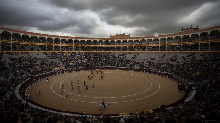 "In this photo taken on Thursday, May 12, 2016, bullfighters and assistants walk along the ring during the ""paseillo"" or ritual entrance to the arena prior a bullfight at the Las Ventas bullring in Madrid, Spain. As matadors face half-ton bulls this month during Madrid's most important annual series of bullfights and Pamplona gears up for its chaotic July bull runs, tensions are building between anti-bullfighting forces and the traditions' defenders. (AP Photo/Francisco Seco)"