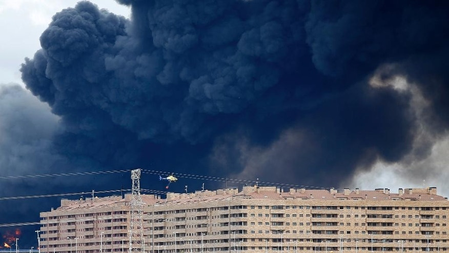 A fire fighting helicopter flies  billowing black smoke rising from behind large housing blocks in Sesena, central Spain, Friday, May 13, 2016. A massive fire is raging at a sprawling tire dump in a town near Madrid, sending a spectacular cloud of thick black smoke into the air that's visible for at least 30 kilometers (20 miles). Ten teams of firefighters are trying to put out the blaze at the tire dump in the town of Sesena, still raging more than 10 hours after it started. (AP Photo/Paul White)