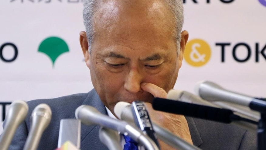 Tokyo Gov. Yoichi Masuzoe scratches his nose reporters questions during a press conference in Tokyo, Friday, May 13, 2016. The governor Tokyo has triggered public outrage for flying first-class and staying at up to $1,800-a-night suites in Europe and America during official overseas trips. (AP Photo/Koji Sasahara)