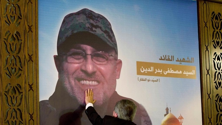 "Adnan Badreddine, brother of top Hezbollah commander Mustafa Badreddine, grieves at his brother's picture in a southern suburb of Beirut, Lebanon, Friday, May 13, 2016. Lebanon's militant Hezbollah group said Friday that its top military commander who was supervising its military operations in Syria, Mustafa Badreddine, was killed in an explosion in Damascus, a major blow to the Shiite group which has played a significant role in the conflict next door. Words in Arabic say ""The martyr commander Mustafa Badreddine"". (AP Photo/Hassan Ammar)"