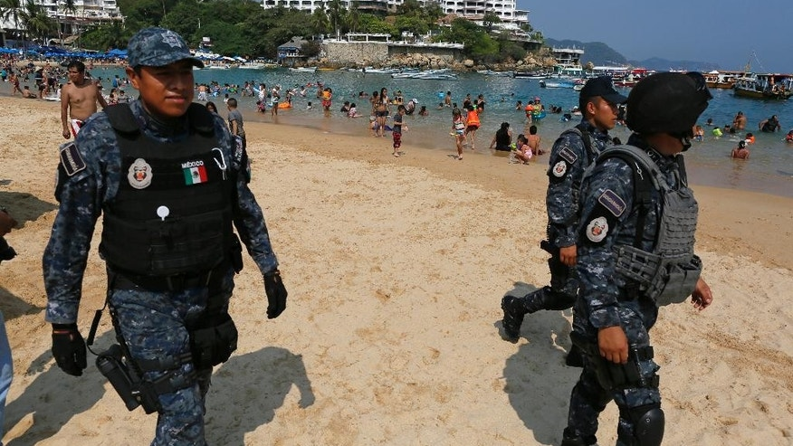 Federal police officer patrol Caleta beach crowded with local residents and tourists in Acapulco, Mexico, Friday, May 13, 2016. The city of Acapulco and Guerrero state in general have experienced a wave of violence attributed to warring drug gangs. On Saturday Mexican authorities say three men were gunned down, in a tourist-hotel quarter of the Pacific resort city. (AP Photo/Enric Marti)