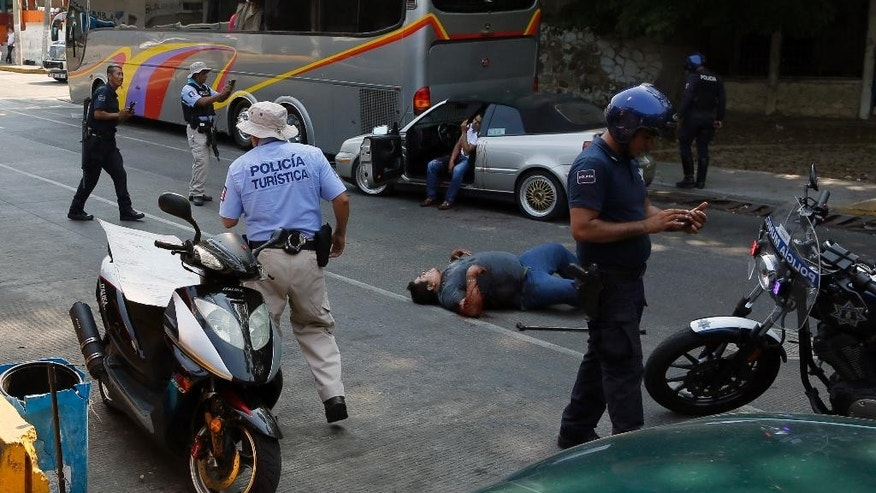 A wounded man lies on the ground and a second one sits in his car waiting for assistance as police arrive to the scene of a shooting near Caleta beach in Acapulco, Mexico, Friday, May 13, 2016. The city of Acapulco and Guerrero state in general have experienced a wave of violence attributed to warring drug gangs. On Saturday Mexican authorities say three men shot dead, in a tourist-hotel quarter of the Pacific resort city. (AP Photo/Enric Marti)