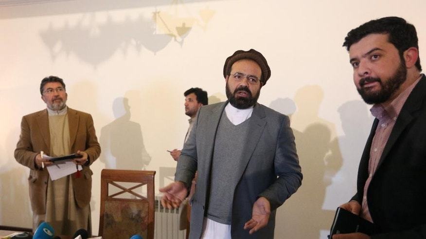 In this Thursday, March 17, 2016 photo, Amin Karim, second right, an official of the Hezb-i-Islami Party, speaks as he leaves after a press conference in Kabul, Afghanistan. An Afghan official says the government will finalize a peace deal with a notorious militant insurgent group within days. Ataullah Saleem, a deputy head of Kabul's High Peace Council, said on Saturday, May 14, an agreement with the armed wing of Hezb-i-Islami could be completed Sunday, after two years of negotiations. (AP Photo/Rahmat Gul)