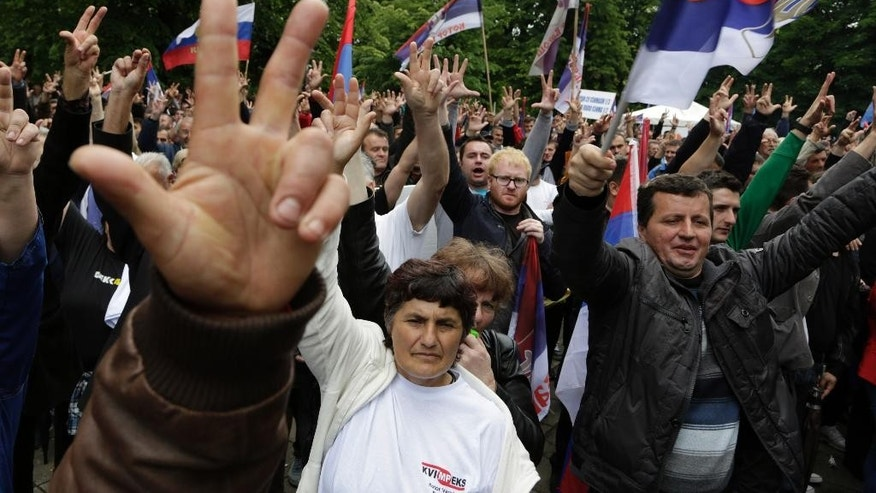 Bosnian Serb people flash three fingers, the Serbian Orthodox sign, during a demonstration in Banja Luka, Bosnia, on Saturday, May 14, 2016. Tens of thousands of people are rallying in separate demonstrations for and against the regional Bosnian Serb government in the city Banja Luka. The pro-EU Alliance for Changes is accusing the Bosnian Serb government of corruption and its leader Milorad Dodik of dictatorship, saying he has brought the region to the brink of financial collapse. Dodik's camp is accusing the opposition of betraying Bosnian Serb national interests. (AP Photo/Amel Emric)