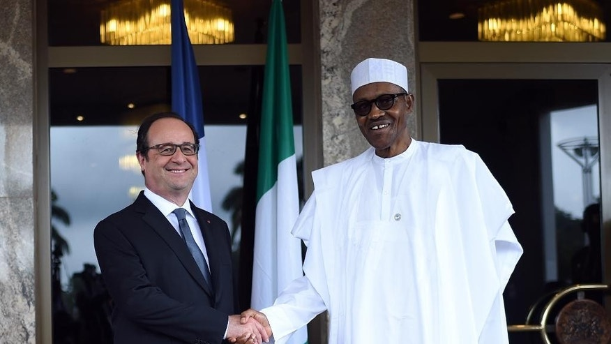 French President Francois Hollande, left, is welcomed by Nigerian President Muhammadu Buhari  upon his arrival in Abuja, Nigeria, Saturday, May 14, 2016.  Hollande is on one day visit to Nigeria to attend a regional security summit. (Stephane De Sakutin/Pool Photo via AP)
