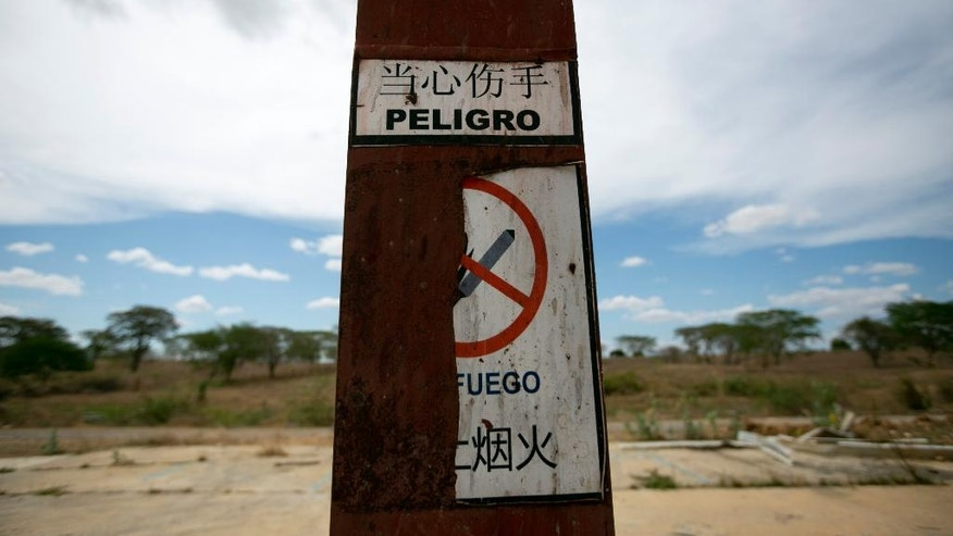 "This March 21, 2016 photo shows a sign warning of ""Danger"" at a railroad factory after it was abandoned by its Chinese managers in Zaraza, Guarico state, Venezuela. A decade ago then-President Hugo Chavez dreamed up the Tinaco-Anaco railway as a way to populate the plains and attract development from long-dominant coastal areas. (AP Photo/Ariana Cubillos)"