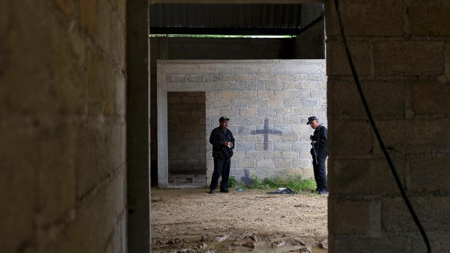 FILE - In this July 3, 2014 file photo, state police stand inside a warehouse where a black cross marks a wall near blood stains on the ground, after a shootout between Mexican soldiers and alleged criminals in Tlatlaya, Mexico. A Mexican civilian court has freed the final three soldiers accused of homicide in the 2014 incident in which suspects were allegedly executed after they surrendered. The federal Attorney General's Office said late Friday, May 13, 2014, the three were absolved of charges of homicide, cover-up and alteration of evidence. (AP Photo/Rebecca Blackwell, File)