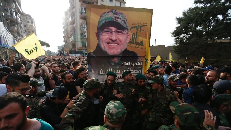 Hezbollah supporters carry the picture of their slain commander Mustafa Badreddine, who was killed in Syria, during his funeral procession in a southern suburb of Beirut, Lebanon, Friday, May 13, 2016. Badreddine died in an explosion in Damascus, a death that is a major blow to the Shiite group, which has played a significant role in the conflict next door. (AP Photo/Hassan Ammar)