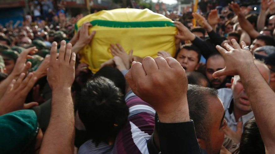 Hezbollah supporters carry the coffin of their slain commander Mustafa Badreddine, draped in a Hezbollah flag, who was killed in Syria, during his funeral procession in a southern suburb of Beirut, Lebanon, Friday, May 13, 2016. Badreddine died in an explosion in Damascus, a death that is a major blow to the Shiite group, which has played a significant role in the conflict next door. (AP Photo/Hassan Ammar)