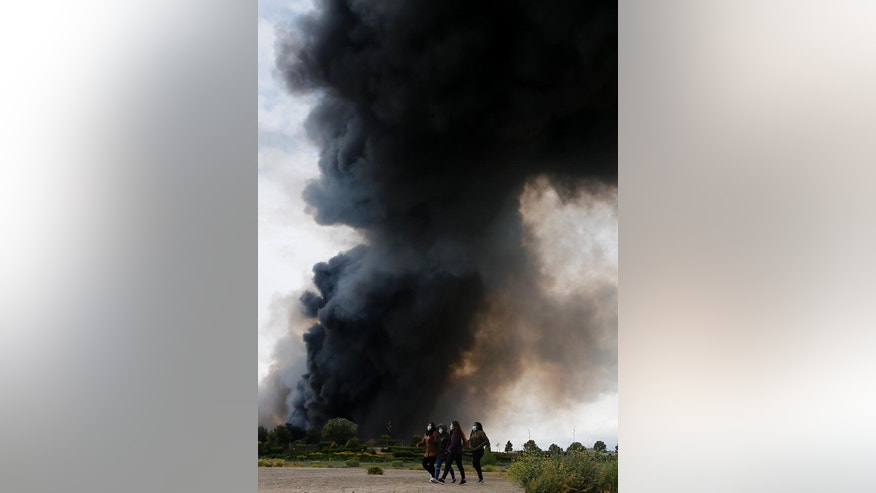 Four women with masks walk away from billowing black smoke from a huge fire in Sesena, central Spain, Friday, May 13, 2016. Spanish officials have ordered the evacuation of 9,000 people living in a sprawling apartment complex close to a raging tire dump fire in a town near Madrid. (AP Photo/Paul White)
