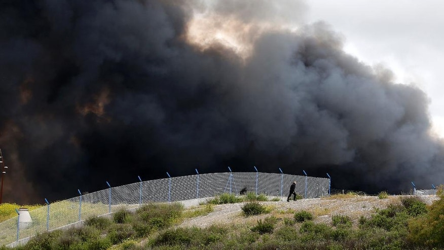 A man walks alongside a fence as smoke billows from a fire in Sesena, central Spain, Friday, May 13, 2016. Spanish officials have ordered the evacuation of 9,000 people living in a sprawling apartment complex close to a raging tire dump fire in a town near Madrid. (AP Photo/Paul White)
