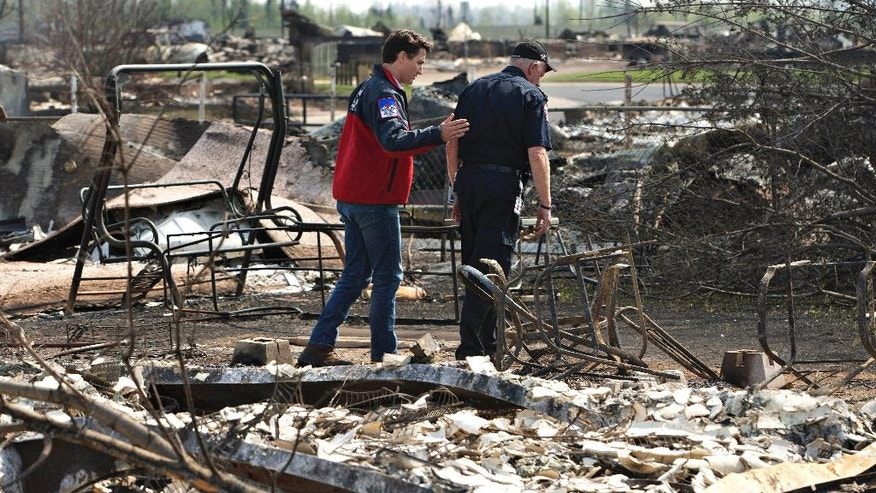 Canadian Prime Minister Justin Trudeau, left, and Fort McMurray Fire Chief Darby Allen look over the devastation during a visit to Fort McMurray, Canada., Friday, May 13, 2016. (Jason Franson/The Canadian Press via AP) MANDATORY CREDIT