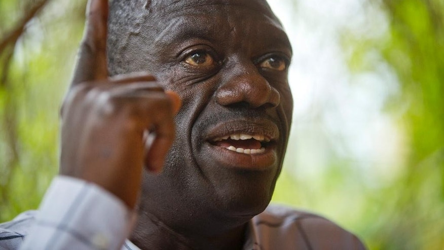 FILE - In this Sunday, Feb. 21, 2016 file photo, opposition leader and presidential candidate Kizza Besigye speaks to the media while under continued house arrest, at his home in Kasangati, outside the capital Kampala, in Uganda. A spokesman for Uganda's judiciary said Saturday, May 14, 2016 that the main opposition leader Kizza Besigye has been flown to Moroto in the remote northeast of the country and charged with treason, a charge which attracts a maximum penalty of death upon conviction. (AP Photo/Ben Curtis, File)