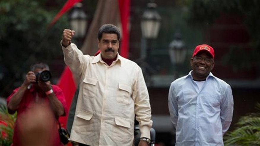 Venezuelas President Nicolas Maduro holds out his right fist while standing next to Vice President Aristobulo Isturiz during a ceremony marking the 206th anniversary of the call for independence from Spain, in Caracas, Venezuela, Tuesday, April 19, 2016. Opposition members are calling for Venezuelans to demonstrate across the country Tuesday to pressure Maduro to leave office. (AP Photo/Fernando Llano)