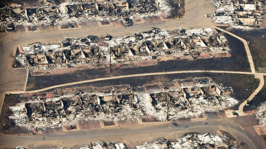 This aerial photo shows a devastated neighborhood in Fort McMurray, Alberta, Canada, on Friday, May 13, 2016.  Prime Minister Justin Trudeau landed in Fort McMurray on Friday and boarded a military helicopter to assess the damage caused by a raging wildfire that forced the evacuation of more than 88,000 people in the country's oil sands capital. (Jason Franson/The Canadian Press via AP) MANDATORY CREDIT