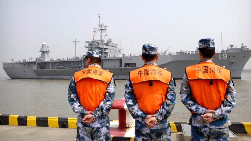 FILE - In this May 6, 2016, file photo, soldiers from the Chinese People's Liberation Army (PLA) Navy watch as the USS Blue Ridge arrives at a port in Shanghai.