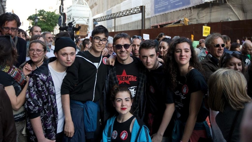The co -funder of the Podemos party, Juan Carlos Monedero, center, poses with youths for photos as protesters march towards the Puerta del Sol plaza in central Madrid, Sunday May 2016. The demonstration is to mark the fifth anniversary of a protest movement that led to the creation of Podemos, now Spain's third most-popular political party. (AP Photo/Paul White)