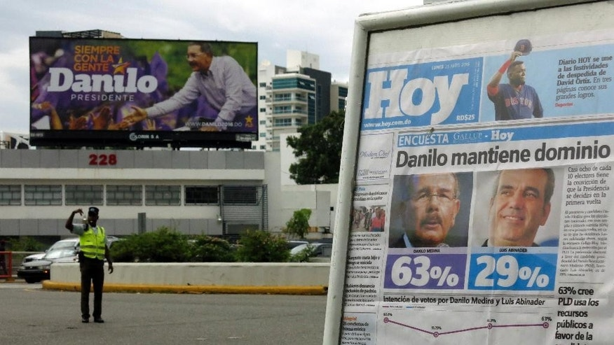 In this April 25, 2016 photo, the front page of Dominican newspaper shows the results of a recent Gallup opinion poll with incumbent, President Danilo Medina ahead in the polls, in Santo Domingo, Dominican Republic. Dominicans face a dizzying array of choices May 15  in one of the most complex ballots in recent history, with eight candidates for president, all 222 members of Congress up for re-election and thousands of people vying for local offices around the country. (AP Photo/Ezequiel Lopez)