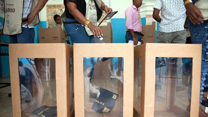 A voter casts her ballot during the presidential, congressional and municipal elections in Santo Domingo, Dominican Republic, Sunday, May 15, 2016. Dominicans faced a dizzying array of choices Sunday in one of the most complex ballots in recent history, with eight candidates for president, all 222 members of Congress up for re-election and thousands of people vying for local offices around the country.(AP Photo/Tatiana Fernandez)