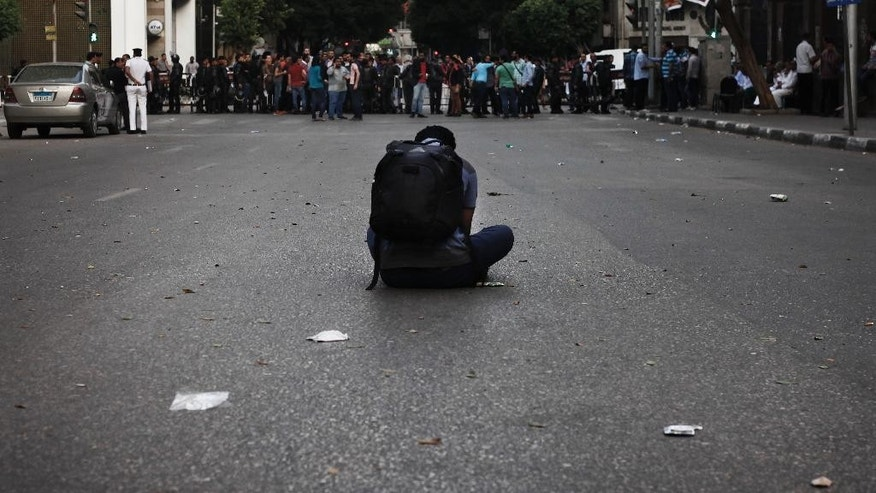 FILE -- In this May 3, 2016 file photo, a journalist takes photos of police as they close off a street leading to the Press Syndicate during a protest in Cairo, Egypt. Egyptian courts on Saturday, May 14, 2016 convicted over 150 protesters for breaking a law that effectively bans demonstrations, sentencing them to up to five years in prison in quick trials that signaled President Abdel-Fattah el-Sissi's resolve to suppress any dissent. The case is rooted in events on April 25 when police stifled planned demonstrations called to protest the government's surrender to Saudi Arabia of two Red Sea islands. (AP Photo/Nariman El-Mofty., File)