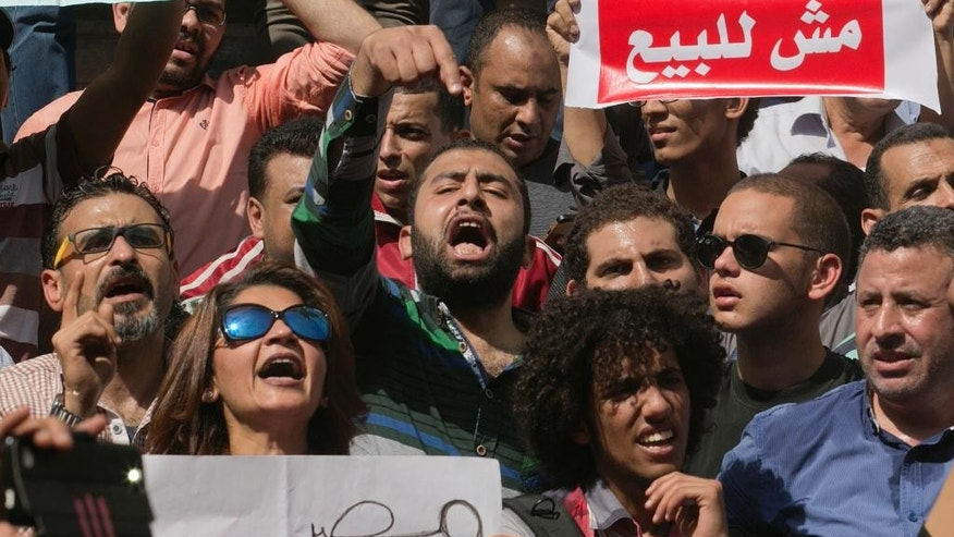 "FILE -- In this April 15, 2016 file photo, Egyptians shout slogans against Egyptian President Abdel-Fattah el-Sissi during a protest against the decision to hand over control of two strategic Red Sea islands to Saudi Arabia in front of the Press Syndicate, in Cairo, Egypt. Arabic reads, ""Egypt is not for sale."" Egyptian courts on Saturday, May 14, 2016 convicted over 150 protesters for breaking a law that effectively bans demonstrations, sentencing them to up to five years in prison in quick trials that signaled President Abdel-Fattah el-Sissi's resolve to suppress any dissent. The case is rooted in events on April 25 when police stifled planned demonstrations called to protest the government's surrender to Saudi Arabia of two Red Sea islands. (AP Photo/Amr Nabil, File)"