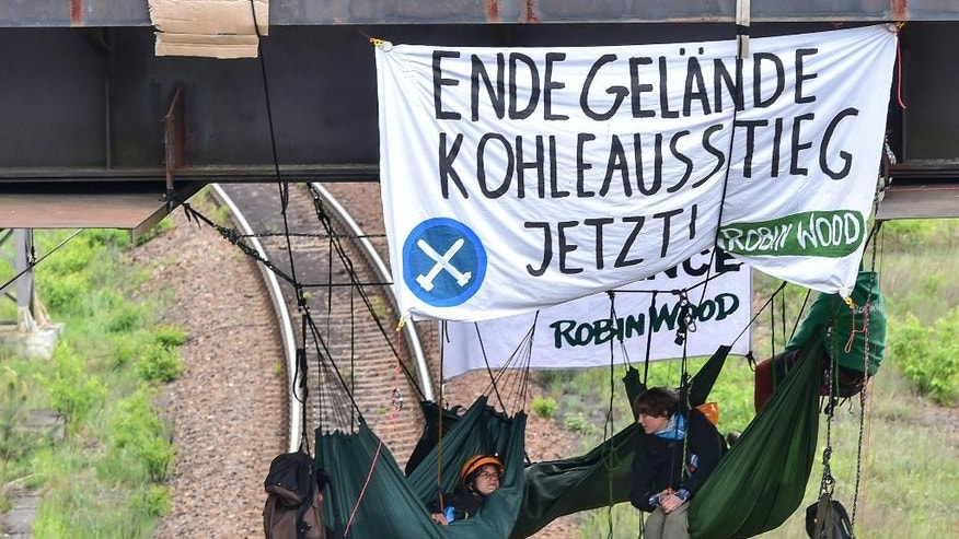 "Activists of the environmental groups Robin Wood and ' Ende Gelaende'   ( It's finished now) hang at a bridge to block the railway tracks near the Vattenfall power plant  in Schwarze Pumpe , eastern Germany, Sunday May 15, 2016. Poster reads""  It's finished now - Stop using coal"" . Police say they have arrested more than 100 people taking part in a demonstration against a coal mining in eastern Germany. Cottbus police say the protesters were among about 300 people who had forced their way onto the site of the Schwarze Pumpe coal-fired power plant late Saturday.   ( Patrick Pleul/dpa via AP)"