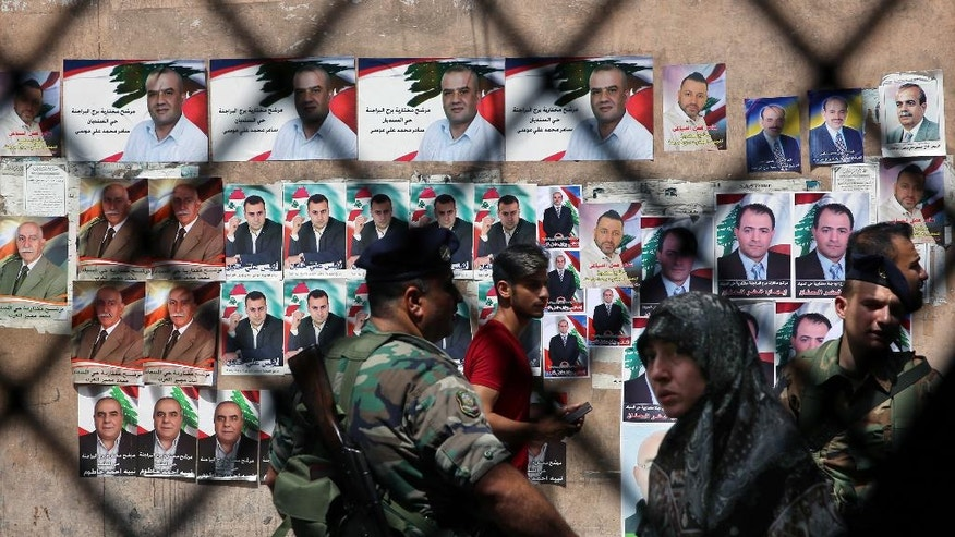 Lebanese citizens and policemen stand next to campaign posters for Beirut municipal candidates in front of a polling station in the southern suburbs of Beirut, Lebanon, Sunday, May 15, 2016. Lebanon is holding the second round of municipal elections Sunday amid a political deadlock that has paralyzed state institutions at the height of a refugee crisis caused by the war in neighboring Syria. Sunday's polls include municipal elections for Beirut's southern suburbs, a Hezbollah stronghold, in a country deeply divided in the group's involvement in the Syria war. (AP Photo/Bilal Hussein)