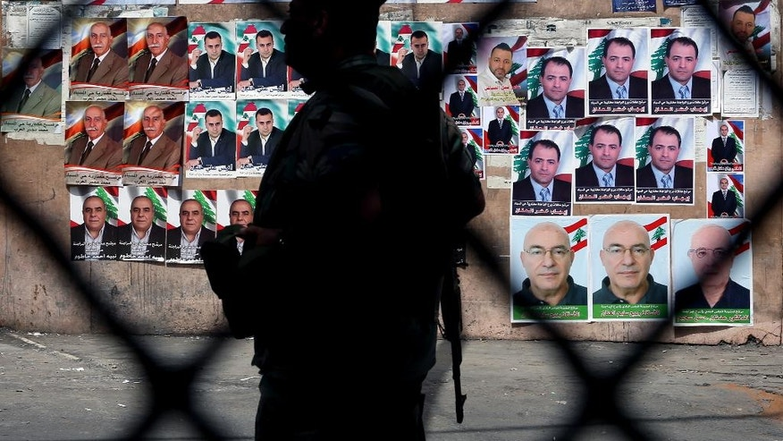A Lebanese policeman stands guard next to campaign posters for Beirut municipal candidates in front of a polling station in the southern suburbs of Beirut, Lebanon, Sunday, May 15, 2016. Lebanon is holding the second round of municipal elections Sunday amid a political deadlock that has paralyzed state institutions at the height of a refugee crisis caused by the war in neighboring Syria. Sunday's polls include municipal elections for Beirut's southern suburbs, a Hezbollah stronghold, in a country deeply divided in the group's involvement in the Syria war. (AP Photo/Bilal Hussein)