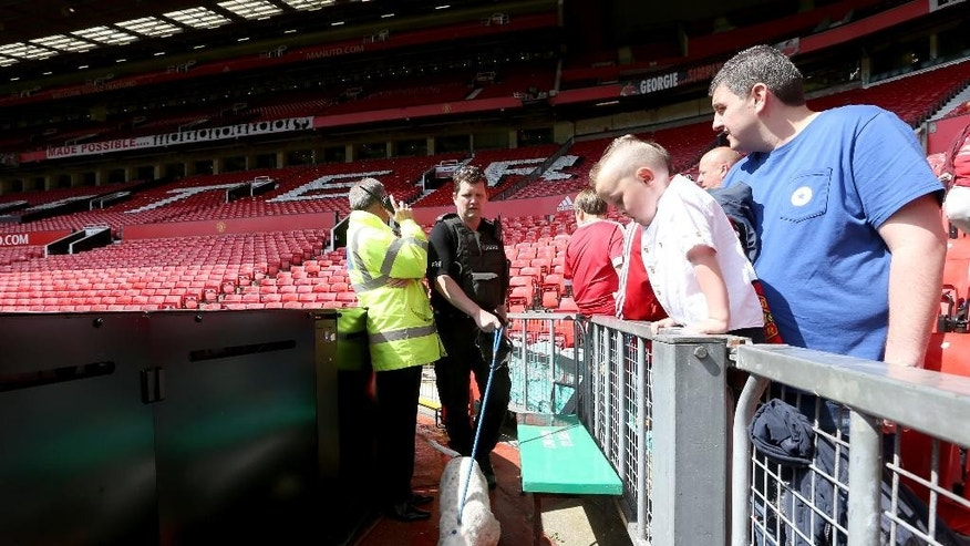 A sniffer dog during the English Premier League match at Old Trafford, Manchester, England. The stadium has been evacuated and the match abandoned after a suspect package was found prior to kick off. Sunday May 15, 2016. Martin Rickett/PA  / PA via AP) UNITED KINGDOM OUT - NO SALES - NO ARCHIVES
