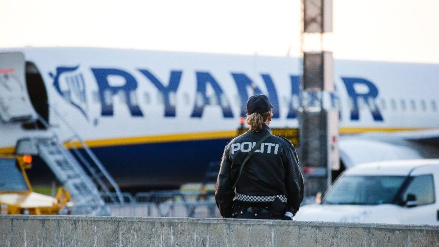 "A police bomb officer stands in front of a Ryanair plane at Moss Airport Rygge, Norway, Sunday, May 15, 2016. Norwegian police say a Manchester-bound plane was evacuated before takeoff due to the ""suspicious behavior"" of two passengers. (Haakon Mosvold Larsen / NTB via AP) NORWAY OUT"