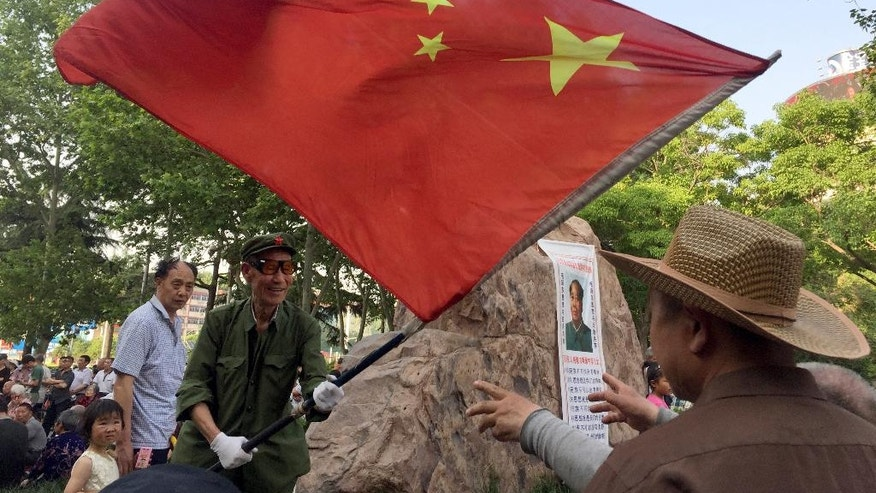 In this photo taken Sunday, May 1, 2016, a supporter of Mao Zedong ideology removes the Chinese national flag after a day of singing and dancing in praise of the late Chinese leader on Zhouwangcheng Plaza in Luoyang in central China's Henan province. In the ancient city of Luoyang, the old, the poor and the marginalized gather daily in the main public square to profess nostalgia for the decade-long political movement, while downplaying that period's violent excesses. (AP Photo/Ng Han Guan)
