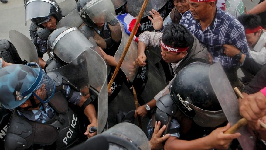 Supporters of Nepal's minority ethnic group wearing headbands with the name of the group try to break through a police cordon, as they protest in a main street leading to the prime minister's office in Kathmandu, Nepal, Sunday, May 15, 2016. Hundreds of minority ethnic group supporters scuffled with police in Nepal's capital on Sunday, restarting protests against the government and the Himalayan nation's new constitution. No one was injured.(AP Photo/Niranjan Shrestha)