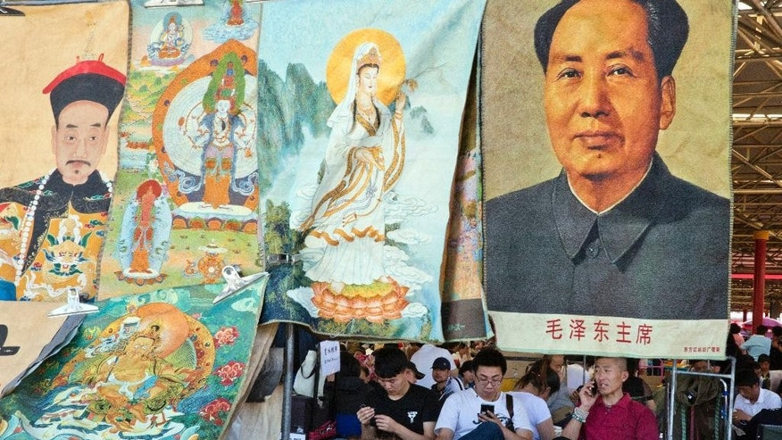 "Vendors wait for customers at a curio market near a display of former Chinese leader Mao Zedong alongside images of emperors and deities in Beijing, China, Monday, May 16, 2016. Exactly 50 years ago, China embarked on what was formally known as the Great Proletarian Cultural Revolution, a decade of tumult launched by Mao Zedong to revive communist goals and enforce a radical egalitarianism. The milestone was largely ignored Monday in the Chinese media, reflecting continuing sensitivities about a period that was later declared a ""catastrophe."" (AP Photo/Ng Han Guan)"