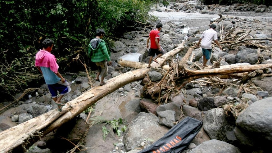 Locals walk near a plastic bag containing the body of a victim of floods in Sibolangit, North Sumatra, Indonesia, Monday, May 16, 2016. Nearly two dozen students are reported missing in the rain-triggered floods and landslides at waterfall in western Indonesia. (AP Photo/Binsar Bakkara)
