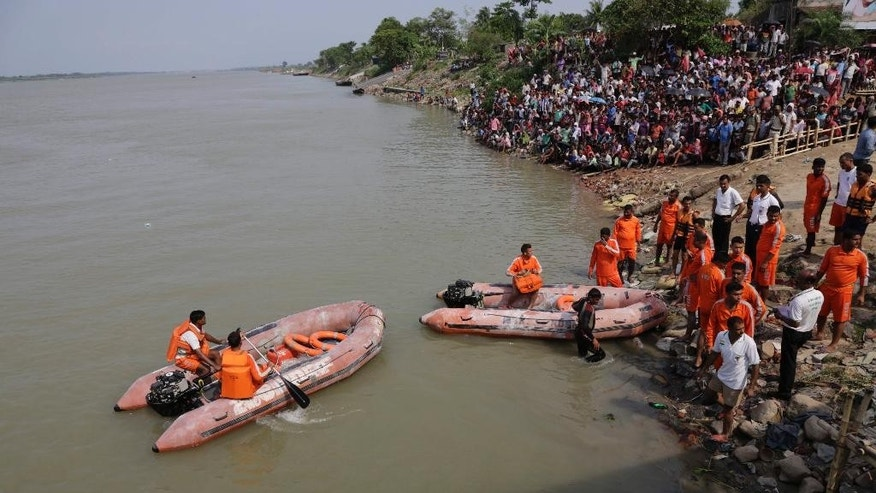 Rescuers of India's National Disaster Response Force (NDRF) search in the river where an overcrowded country boat capsized.