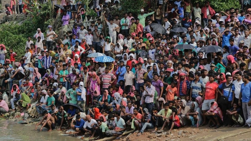 Villagers gather on the banks to watch rescuers.