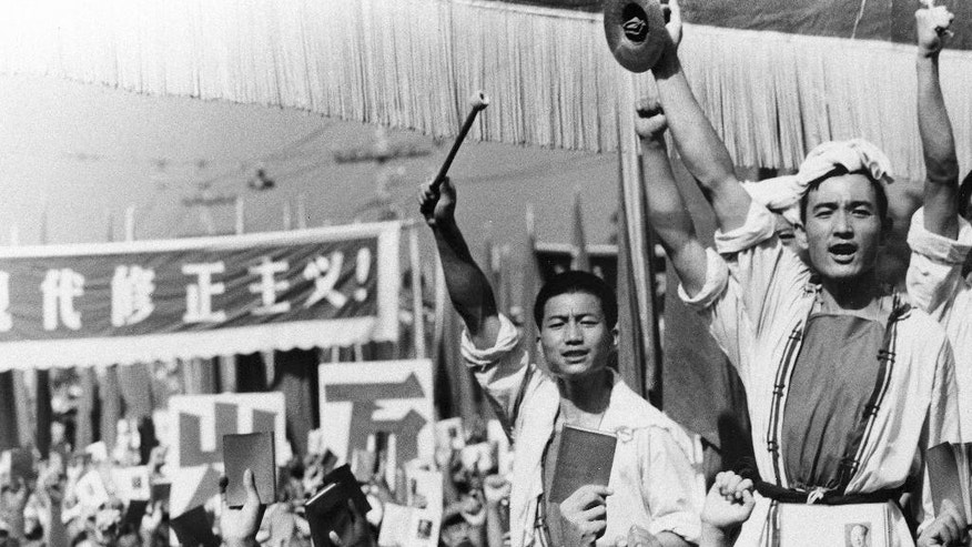 Drummers raise their cymbals and sticks as others hold up small booklets containing the writings of then-Chairman Mao Zedong in 1966.