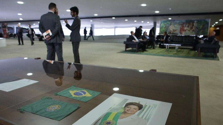 A poster with the photo of Suspended Brazilian President Dilma Rousseff is seen at the Planalto Presidential Palace, during a meeting bewtween Brazil's acting President Michel Temer and trade unions, on the government's proposal for Social Security reform, at the Planalto Presidential Palace, in Brasilia, Brazil, Monday, May 16, 2016. Temer called for the unions to meet Monday to discuss reforms to the country's pension system. (AP Photo/Eraldo Peres)